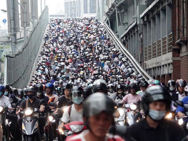 過去10年來,累計有3235人戴上安全帽仍因車禍死亡,立委邱顯智要求增列交通事故受傷、死亡者所戴的安全帽款式,圖為台北大橋上班機車車潮。圖/聯合報系資料照片