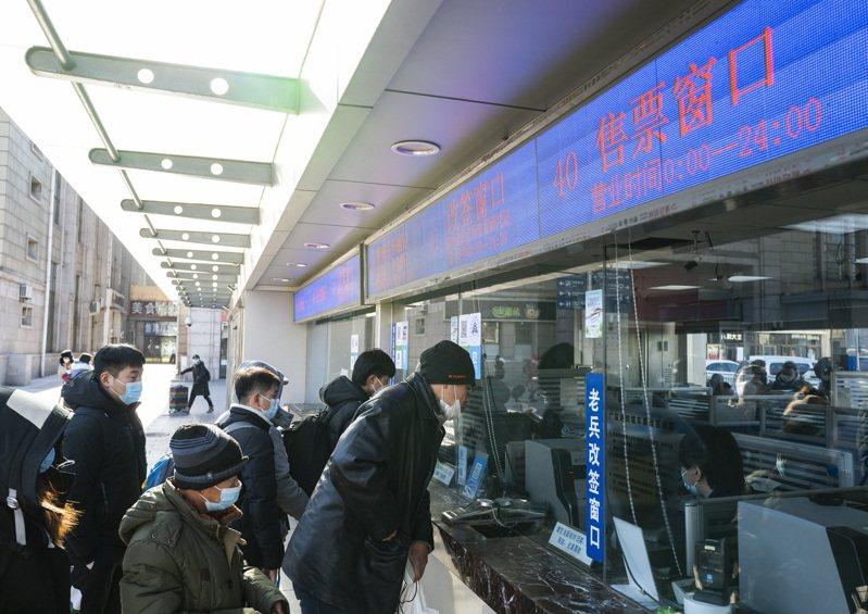 2021年中國春運火車票開始發售。2021年春運自1月28日開始,3月8日結束,共40天,全國鐵路預計發送旅客4.07億人次,日均發送旅客1018萬人次。圖為乘客在北京火車站售票窗口排隊購票。  中國新聞社