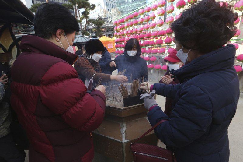 南韓首爾民眾在元旦戴口罩前往曹溪寺上香慶祝新年。(美聯社)