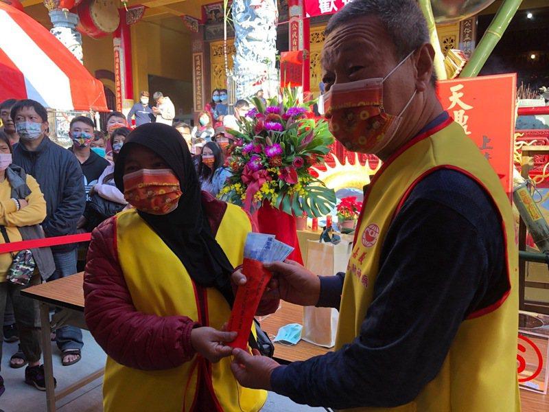 歡喜財神廟千人擲筊大賽,印尼女移工(左)以連續8個聖筊獲得第二名。記者莊祖銘/翻攝