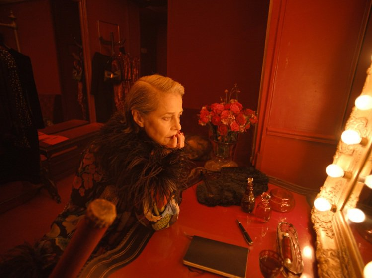 夏洛特蘭普林扮演著在後台等待上台的表演者,穿上印花羽毛裝飾洋裝,像有著無邊魔法一...