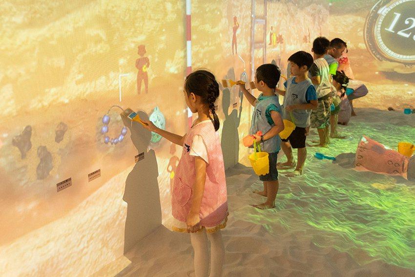 小朋友在魔幻考古沙坑投影文化層發掘古物。 十三行博物館/提供