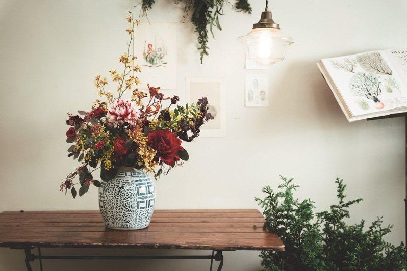 將紅、黃兩色花卉交疊使用,搭配古典花器,彰顯年節喜氣感。 (圖/張晋瑞)