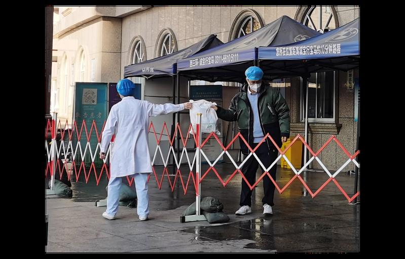 大陸河北省近日又爆發疫情,但官方態度輕忽引發眾怒。圖為河北醫科大學附屬第二醫院急診樓5日封閉後,工作人員隔著栅欄交接物品。中新社