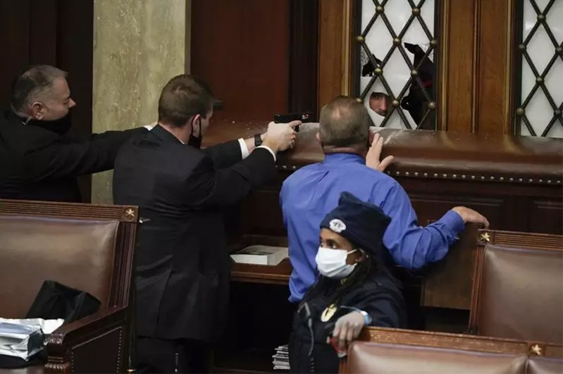 警察拿著槍阻止挺川支持者進入國會大廈眾院內。 美聯社