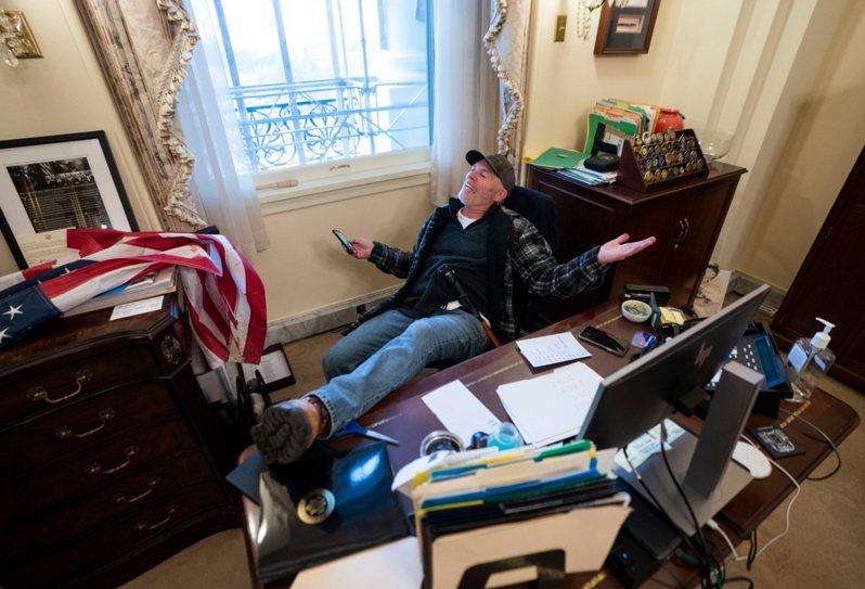 川普支持者闖入眾議院議長波洛西的辦公室,坐下來把腳翹上辦公桌。 歐新社