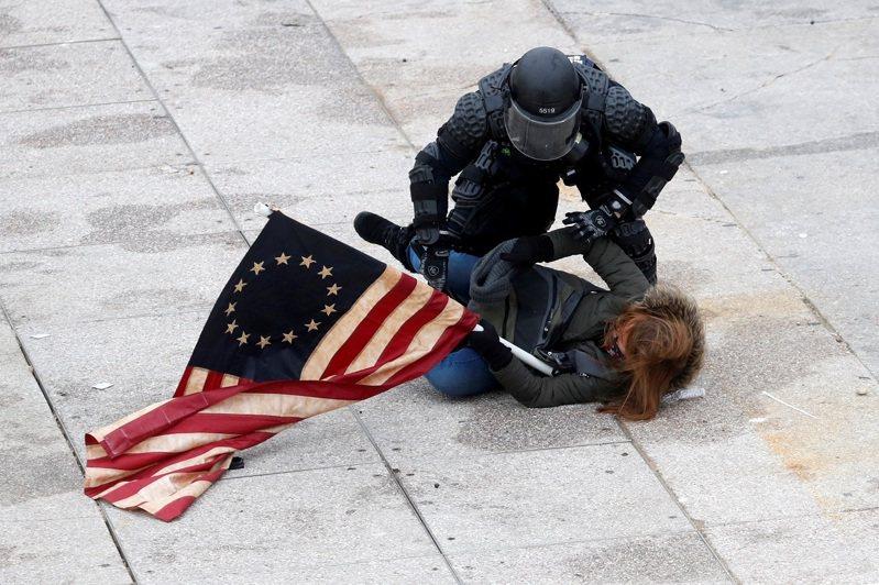 美國總統川普的大批支持者6日衝擊國會,一名川粉被警察壓制在地。路透