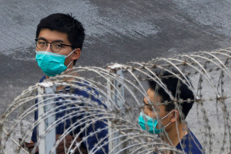繼六日大規模拘捕五十三名香港民主派人士後,昨天港警再拘捕前眾志秘書長黃之鋒(左)。(路透)