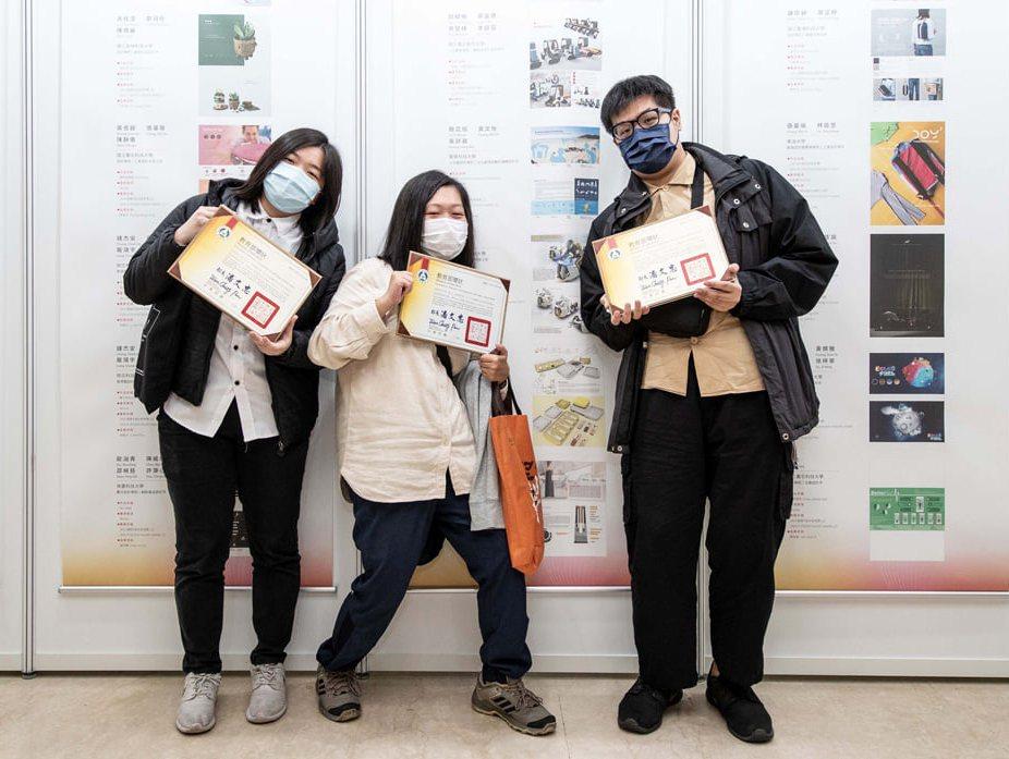 龍華文創系學子與獲獎作品背板合影。龍華科大/提供