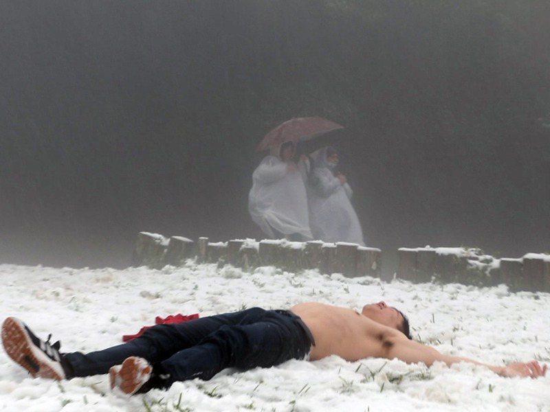 陽明山凌晨開始下雪,吸引許多人上山賞雪,一名男子裸著上半身往雪裡躺,讓路過的賞雪民眾直呼好猛。記者蘇健忠/攝影