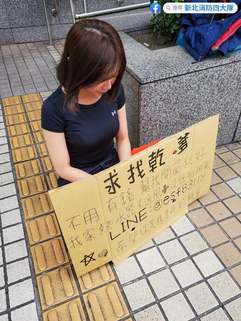 一名身穿短袖緊身上衣的正妹,坐在捷運站外舉牌「求找乾爹」。圖/翻攝自臉書粉專《新北消防四大隊》