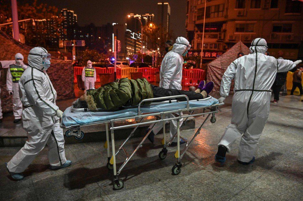 圖為2020年1月的武漢,身穿防護裝備的醫療人員將感染病毒的患者送到醫院。 ...