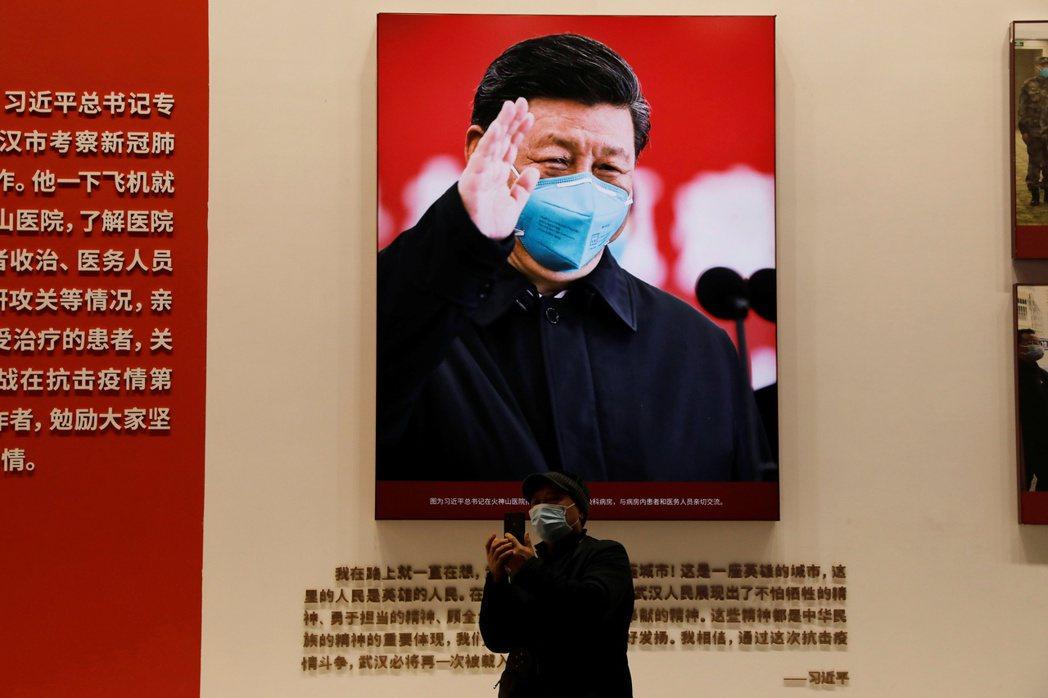 圖為武漢的抗疫特展,一名民眾與身後習近平的肖像合照。  圖/路透社
