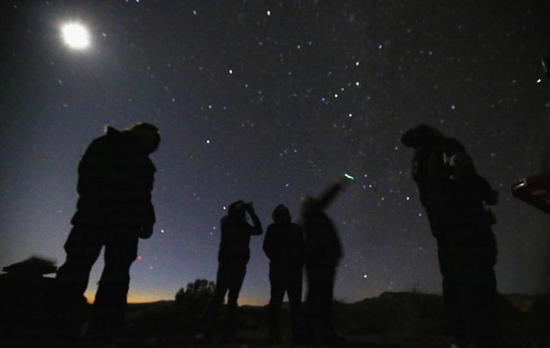 民眾在美國亞利桑那州沙漠中,用夜視鏡尋找UFO。(路透)