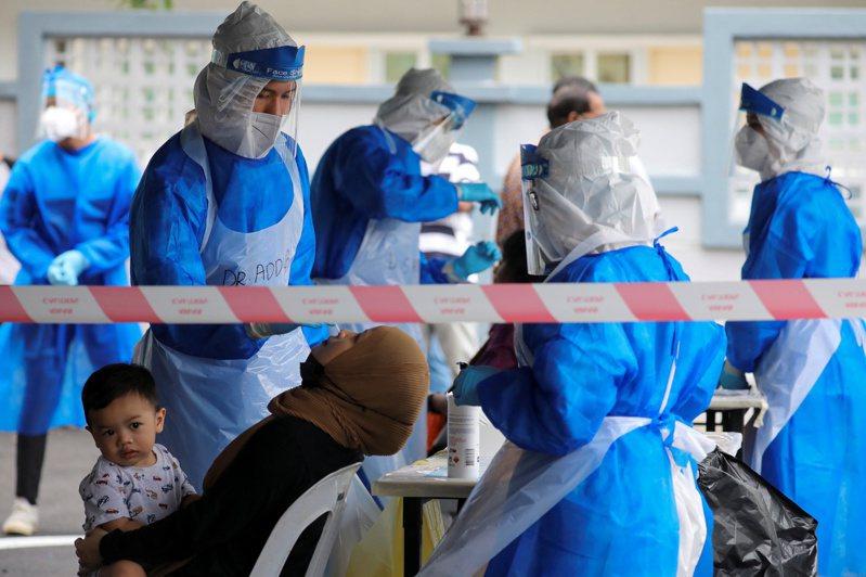 馬來西亞醫護人員為民眾採檢新冠病毒。  路透