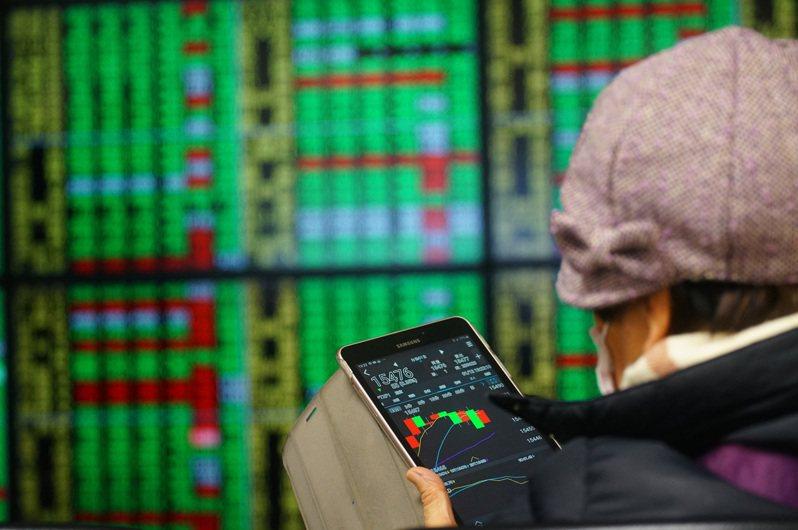 台北股市12日開低震盪走低,投資人拿著平版電腦緊盯盤勢,指數終場下跌56.60點,收在15,500.70點。中央社