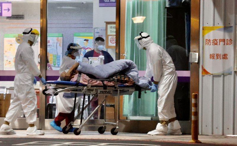 我國爆第二起院內感染,桃園某醫院一位卅餘歲醫師照顧病人時染疫,並傳染給同居護理師女友。圖為全身穿著防護裝備的醫護人員,在篩檢站為病患篩檢。記者許正宏/攝影