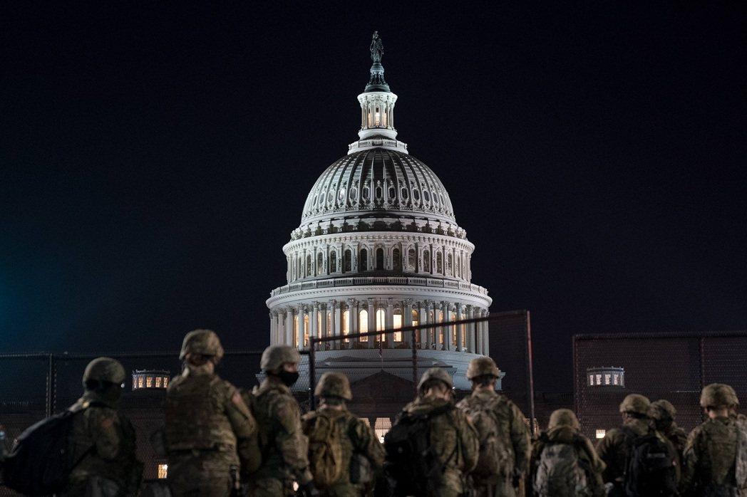 美國國民兵部隊12日晚間在國會山莊外駐守。法新