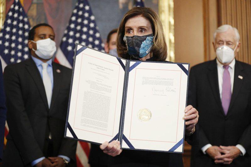 美國眾議院議長裴洛西13日手持眾院通過的對美國總統川普彈劾書。  歐新社