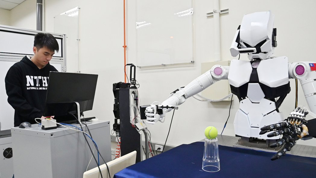 清華大學動機所博士生李俊則寫程式教機器人動作。圖/清大提供