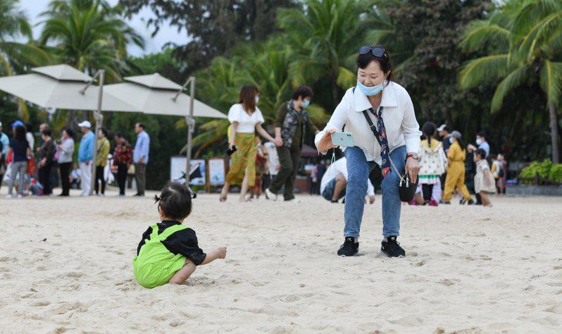 2020年海南旅遊接待大陸國內外遊客6500萬人次,是疫情影響下大陸旅遊恢復情況最好的地區之一。圖為遊客在海南三亞天涯海角景區遊玩。(新華社)