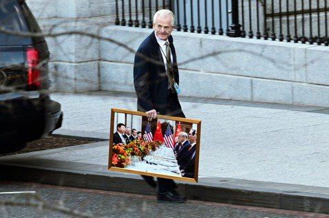 強硬的總統經濟顧問納瓦羅,13日在離開白宮時,手扛著一幅「川普對決習近平」的歷史...