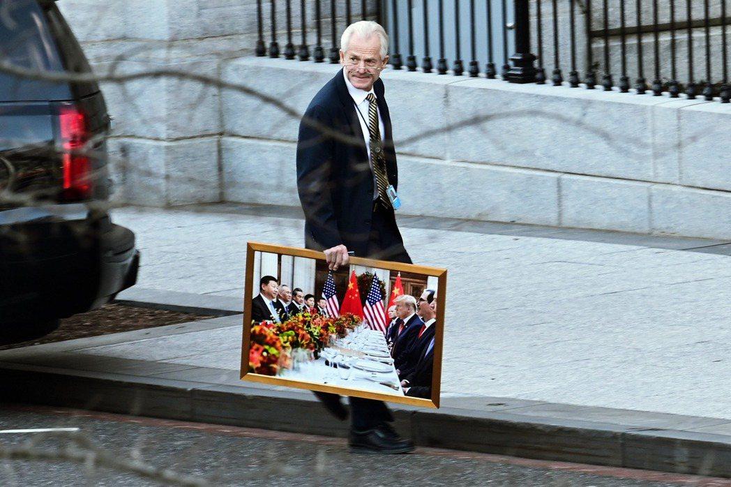 强硬的总统经济顾问纳瓦罗,13日在离开白宫时,手扛着一幅「川普对决习近平」的歷史...