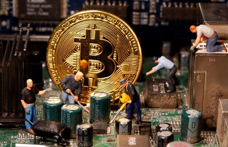 虛擬貨幣比特幣與玩具可動人偶被放在電腦主機板上,攝於7日。路透/Dado Ruvic