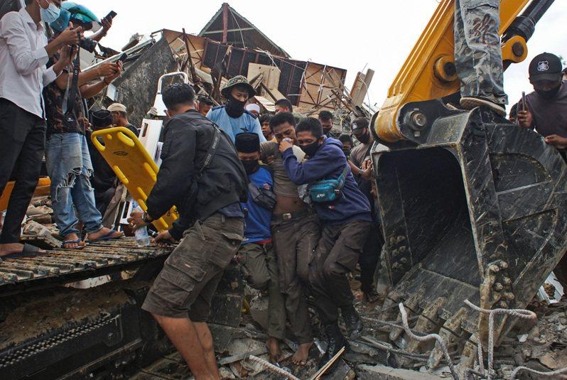 搜救團隊從瓦礫堆中救出當地居民。美聯社