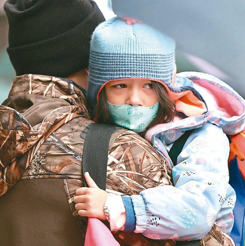 圖為在濕冷低溫中,穿保暖衣物的女孩依偎在父親懷裡,臉上卻掛著淚。聯合報資料照/記者侯永全攝影