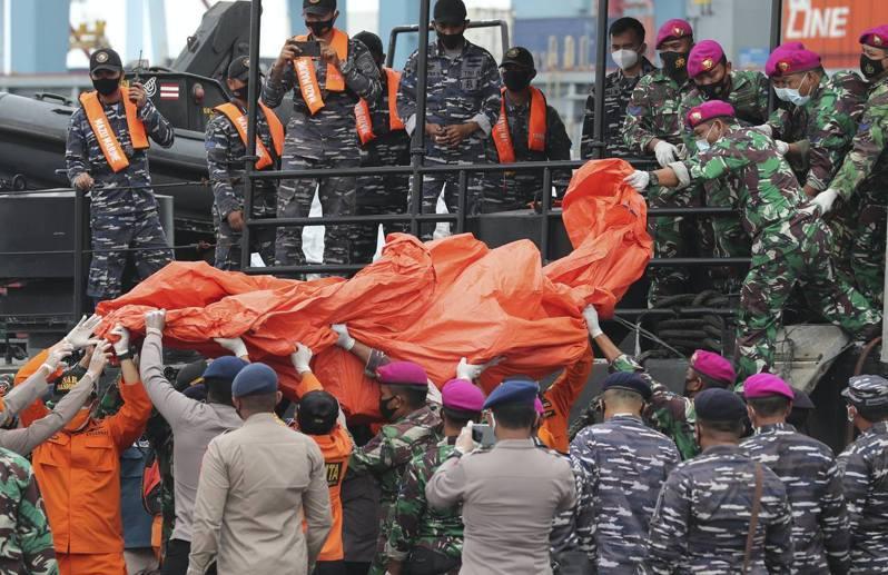 1月10日,在印尼雅加達的丹戎不碌港,士兵和警察用帆布帳篷搬運在爪哇島附近海域發現的殘骸。(AP)