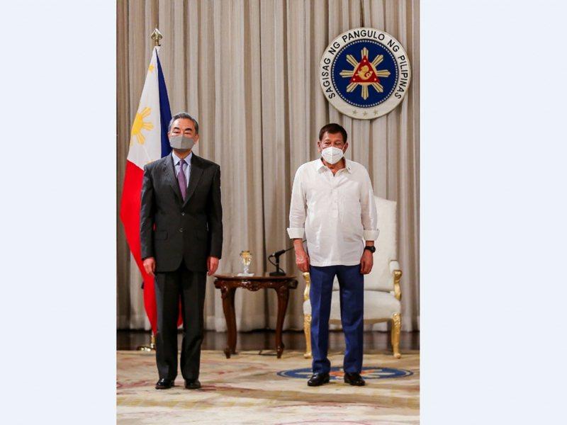 菲律賓總統杜特蒂(右)在馬尼拉會見到訪的中國外長王毅(左)。(新華社)