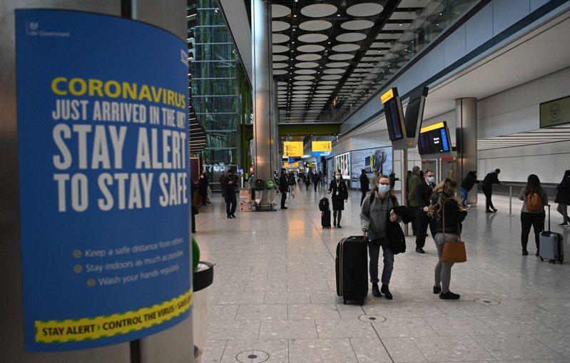 英國擔心巴西變種病毒入侵,在格林威治時間十五日清晨四時起,禁止來自南美洲、巴拿馬、葡萄牙及非洲維德角共和國的旅客入境。圖為英國倫敦附近希斯洛機場國際航班入境區域旅客。(歐新社)