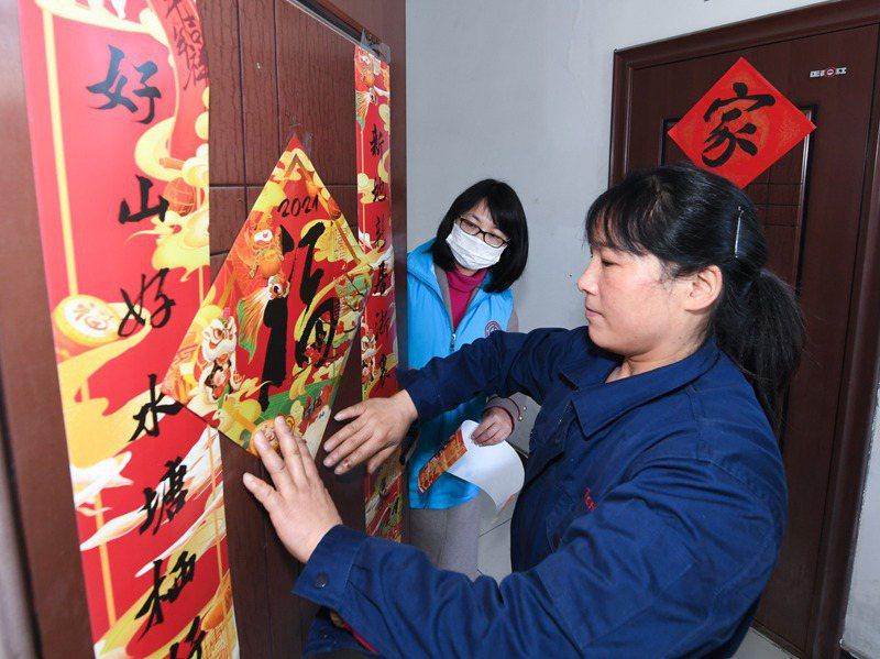 留下來過年的員工把對聯貼在宿舍門上。新華社