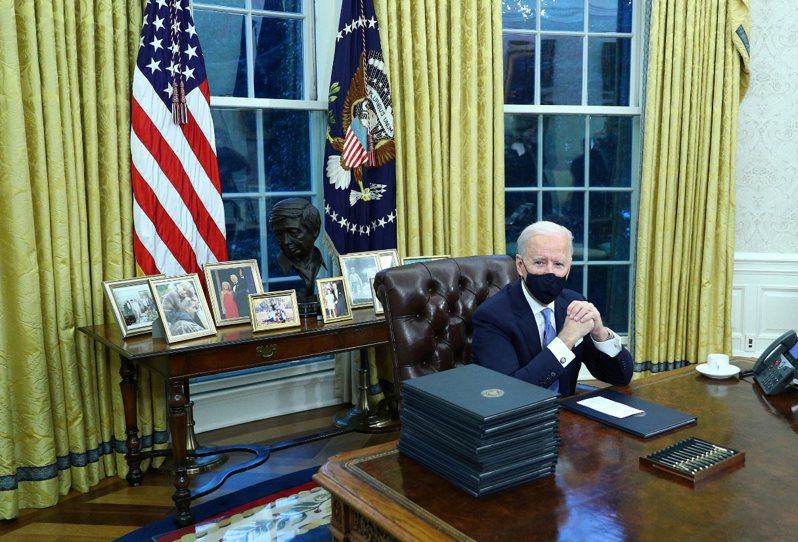 拜登在白宮橢圓辦公室簽署就任總統後首批行政命令。 路透社