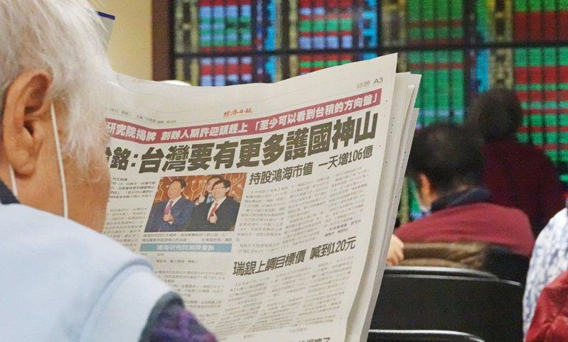 投資人拿出報紙一面看盤一面看著相關報導。記者杜建重/攝影