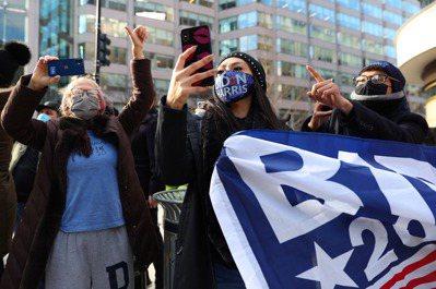 支持民眾上街慶祝拜登上任,一邊看著手機直播就職典禮。(圖/歐新社)