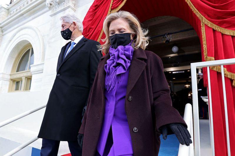 希拉蕊(圖右)身穿紫色西裝、長褲和圍巾,外面再套一件紫紅色大衣。法新社