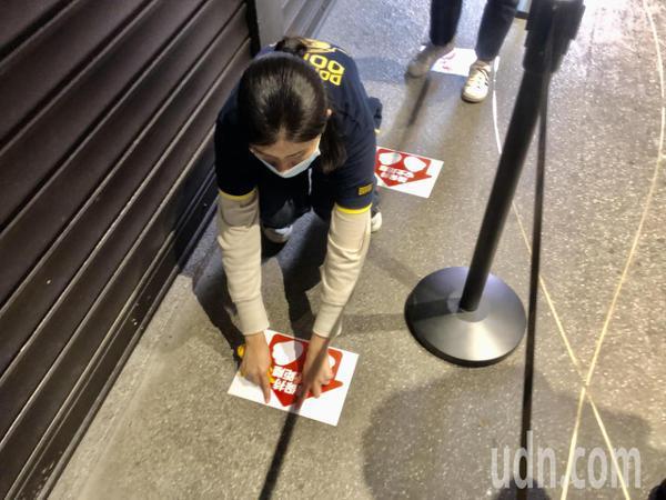 唐吉軻德員工正在地面上貼社交距離的標示。記者鍾維軒/攝影