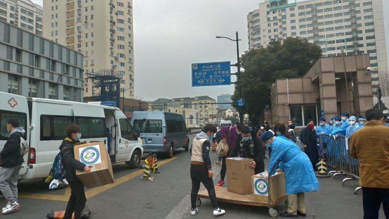 一批醫護人員從上面搬下一箱箱上面貼有「上第六人民醫院」標誌的醫療物資,然後推進醫院。特派記者林宸誼/攝影
