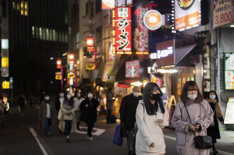 日本東京民眾十四日戴著口罩經過餐廳和酒吧林立的街頭。(美聯社)