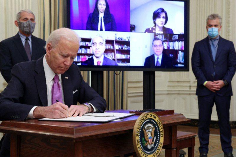 拜登(前)20日簽署「100日口罩挑戰」的行政命令,美國防疫首長佛奇就在身後。路透社