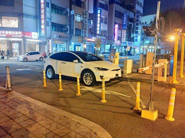 白色特斯拉停在停車場入口處的柵欄前一動也不動,裡面也沒有人,影響人車進出。圖/取...