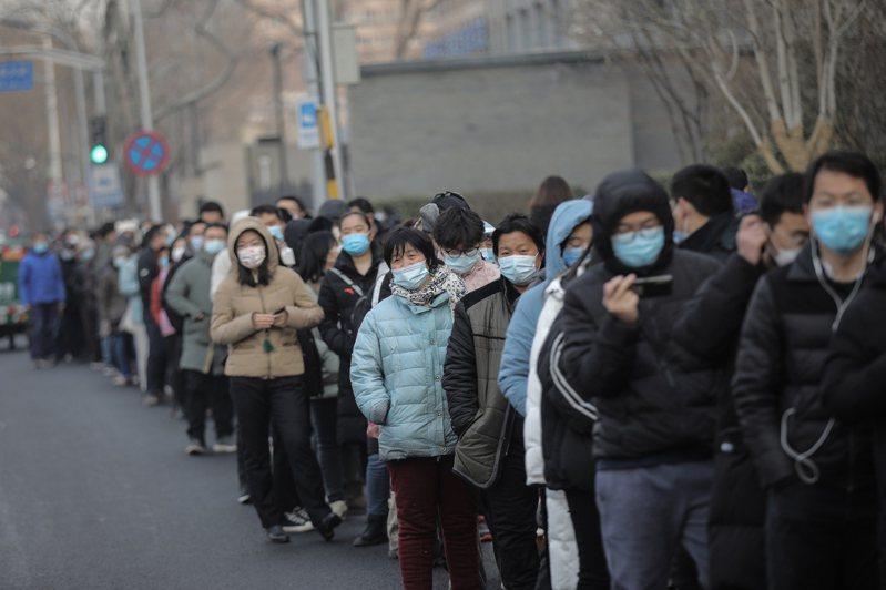北京又新增三例本土病例,北京市中心的東城區和西城區,昨宣布啟動區內全員核酸檢測。圖為北京民眾在寒風中排隊等候檢測。(歐新社)
