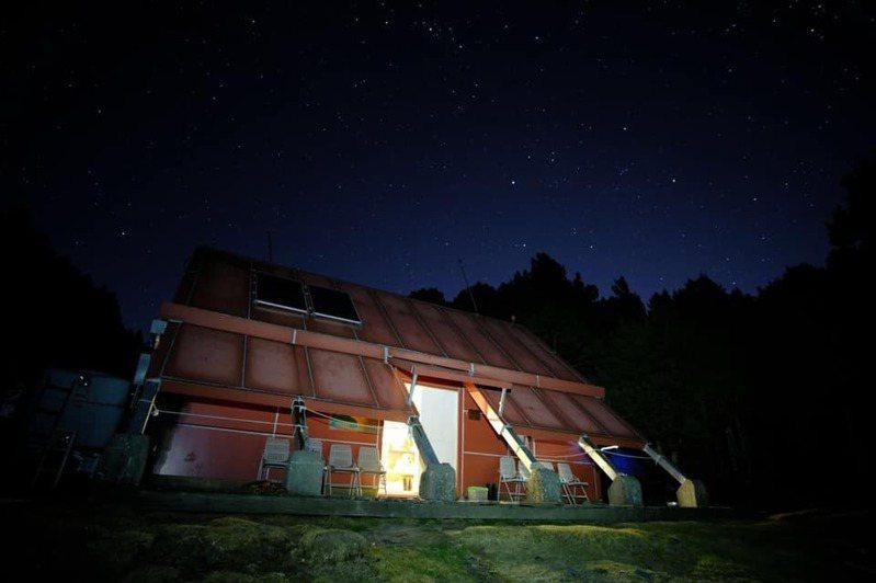 玉山保育志工在零下低溫環境下,完成馬博山屋電力系統修復,入夜後重現光明。圖/玉管處提供