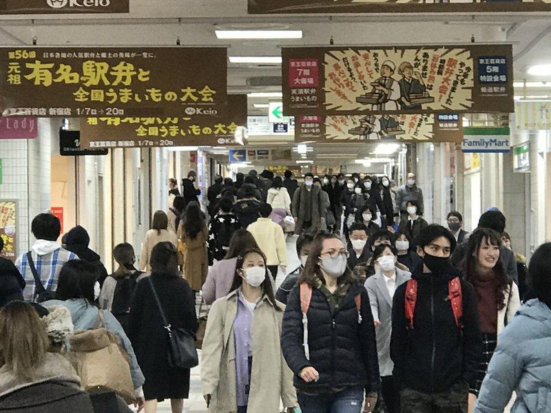 日本東京都今天新增確診病例已稍降,睽違12天減少到3位數。圖為東京新宿車站地下街週末人潮。中央社