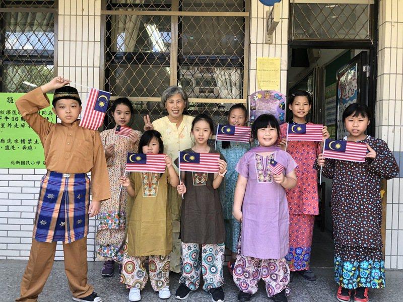 新北市馬來語黃寶雲老師(後排中)認為,在語言課中,融入生活和體驗五感相當有助學習,也可從教學過程中感受到老師的愛心。圖/新北市教育局提供