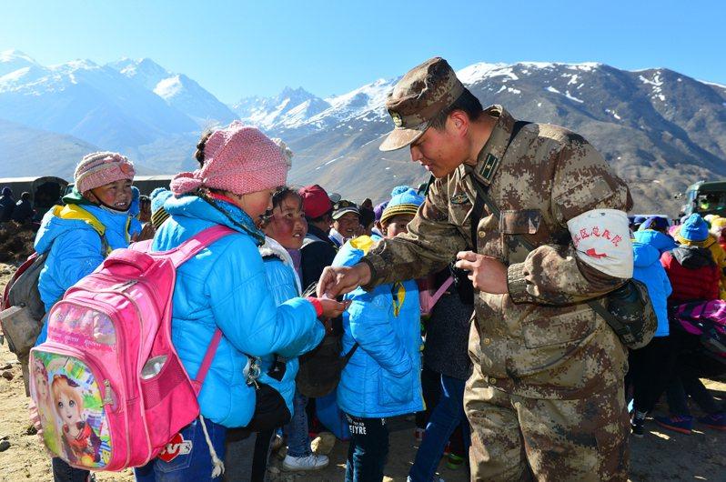 退役3年多的西藏兵李兵(化名)說,中印衝突從去年夏天進入2021年年初零下40度的隆冬,極端考驗部隊的體能與意志。圖為解放軍軍醫在西藏發放防暈車藥。 新華社