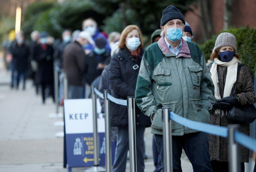 英國正加快疫苗接種速度,圖為22日倫敦羅德板球場外排隊等待接種疫苗的長長人龍。路...