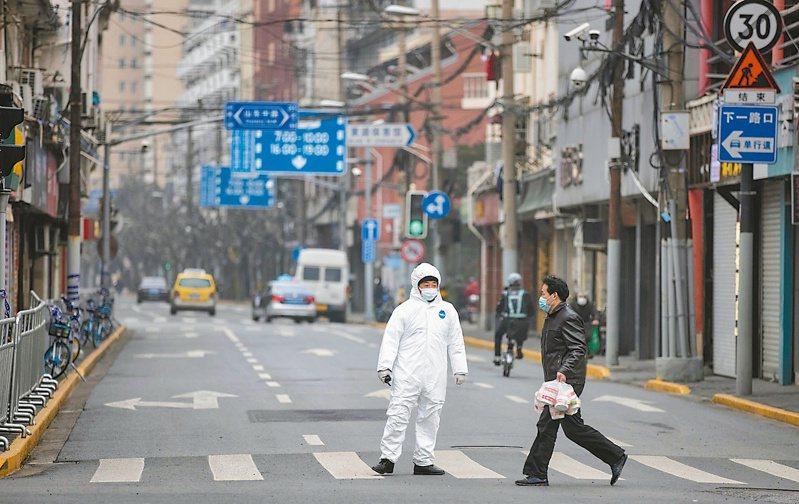 上海將今年經濟長目標設在百分之六以上,但近期又出現本土確診病例,防疫壓力升高。圖為一名路人走過上海仁濟醫院封鎖區附近。(歐新社)